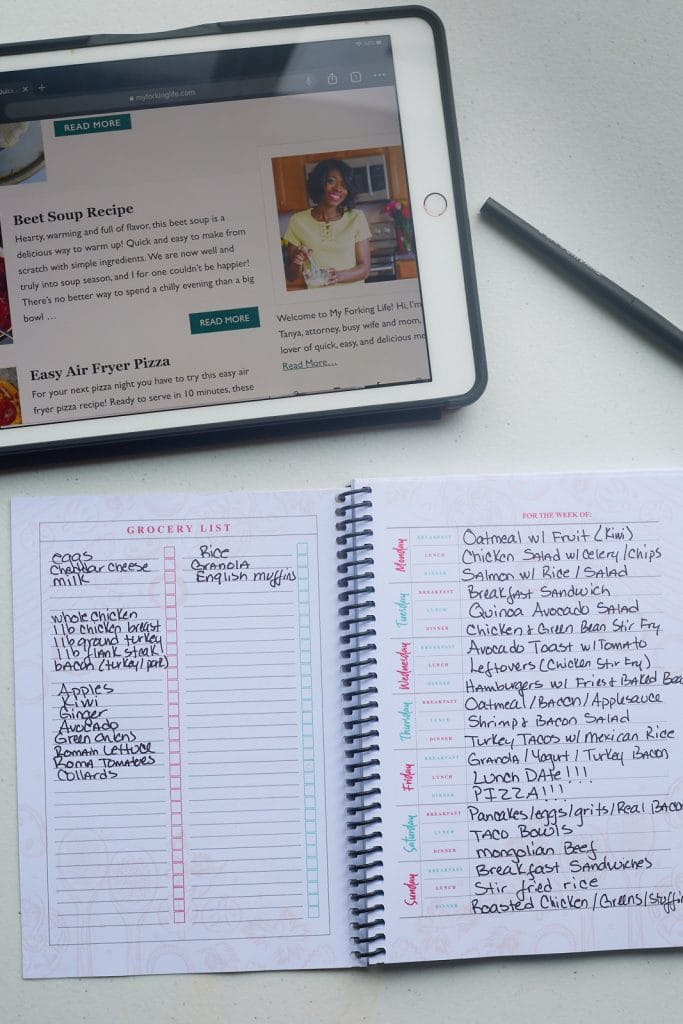 ipad with website on it and weelpy meal planner on white table