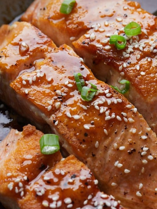 teriyaki salmon in a pan with green onion and sesame seed on top