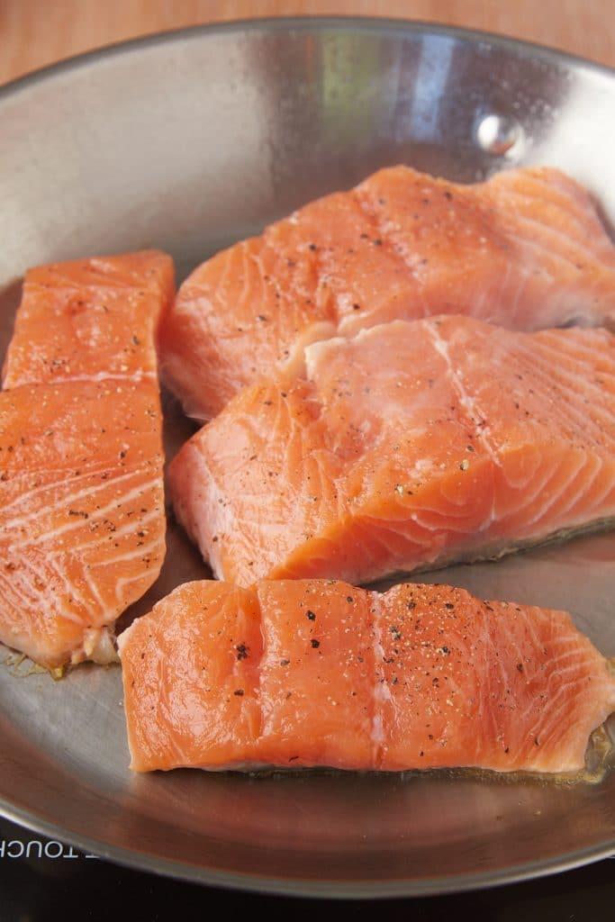 Raw salmon skin side down in a pan.