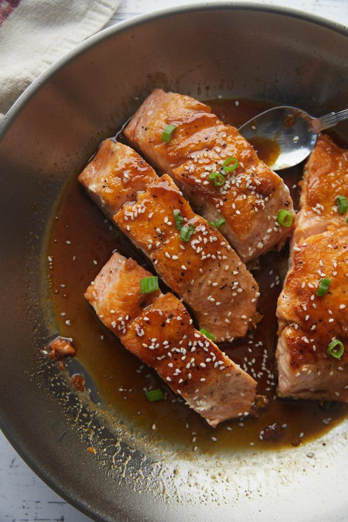 The cooked salmon teriyaki in a skillet.