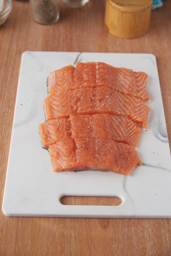A fillet of salmon cut into 4 pieces.