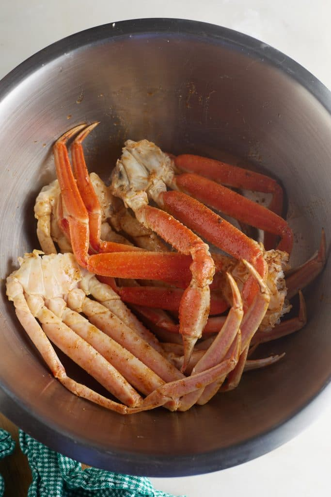 Crab legs with seasonings in a silver bowl.