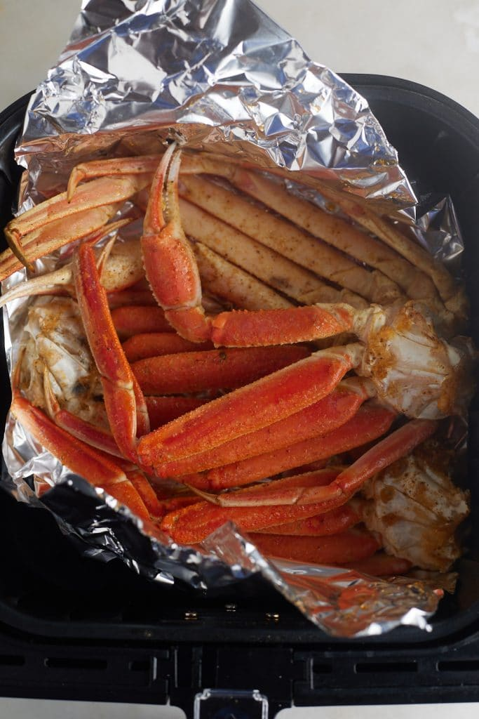 The cooked crab legs on foil in the air fryer basket.