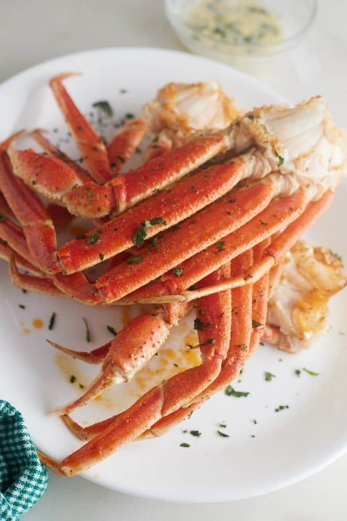 Air fryer crab legs on a white plate and garnished with herbs.