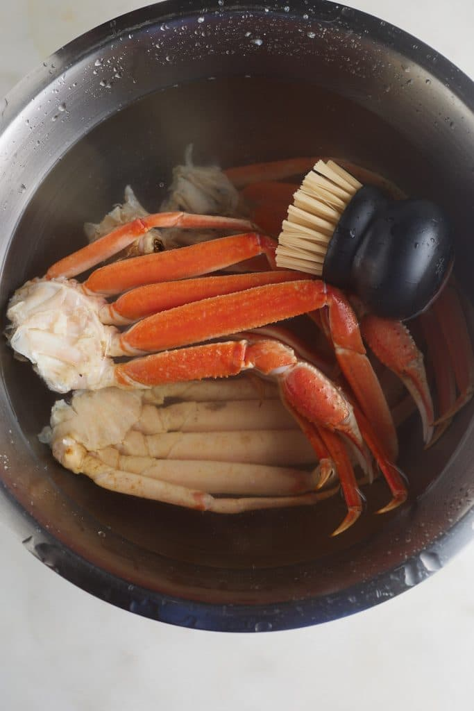 crab legs in large bowl with water and scrubber