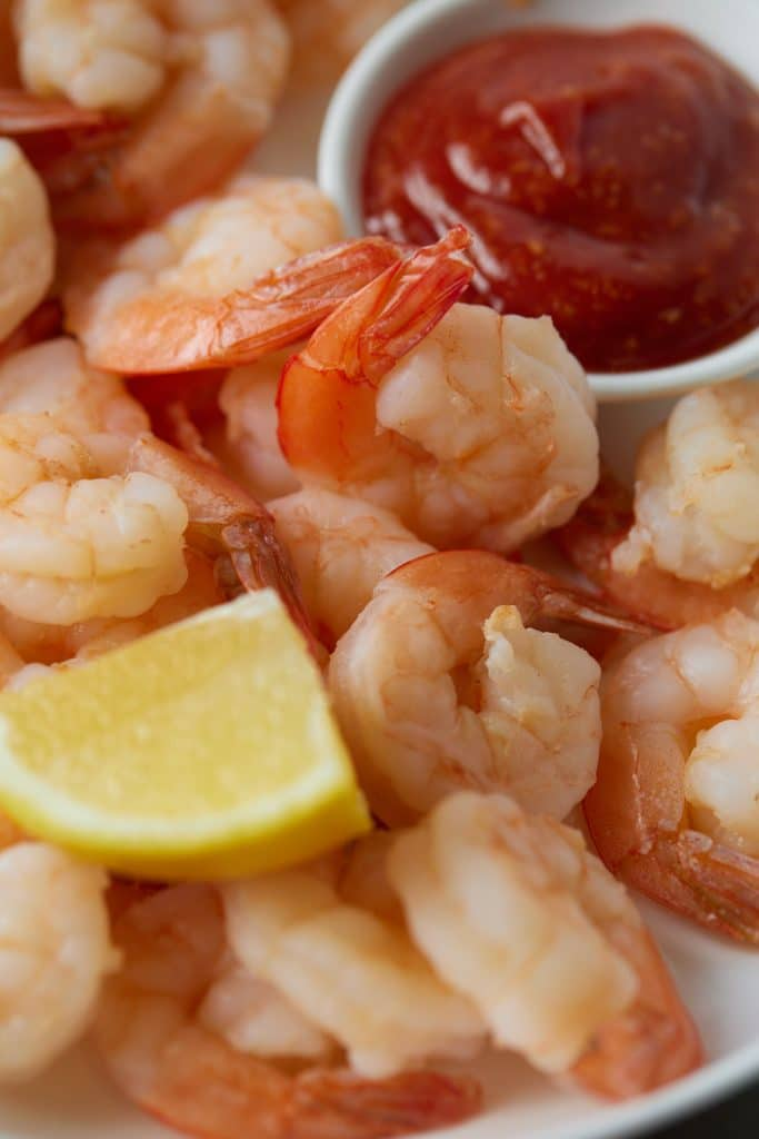Close up of cooked shrimp served with cocktail sauce and a lemon wedge.