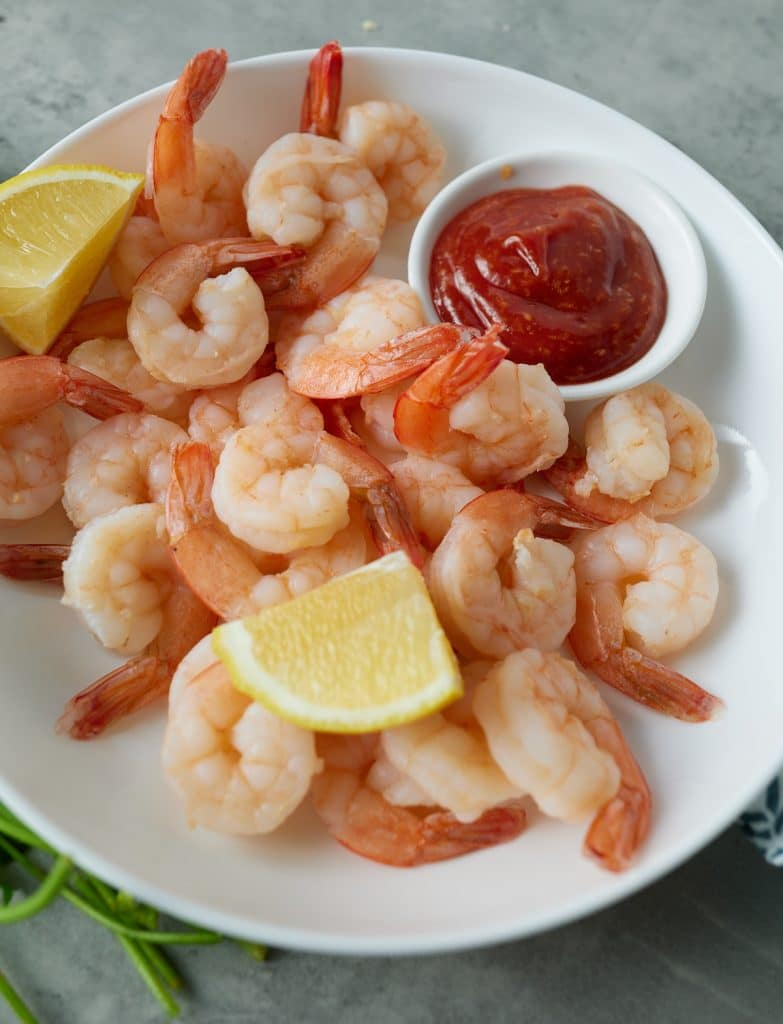 Cooked shrimp and cocktail sauce on a plate.