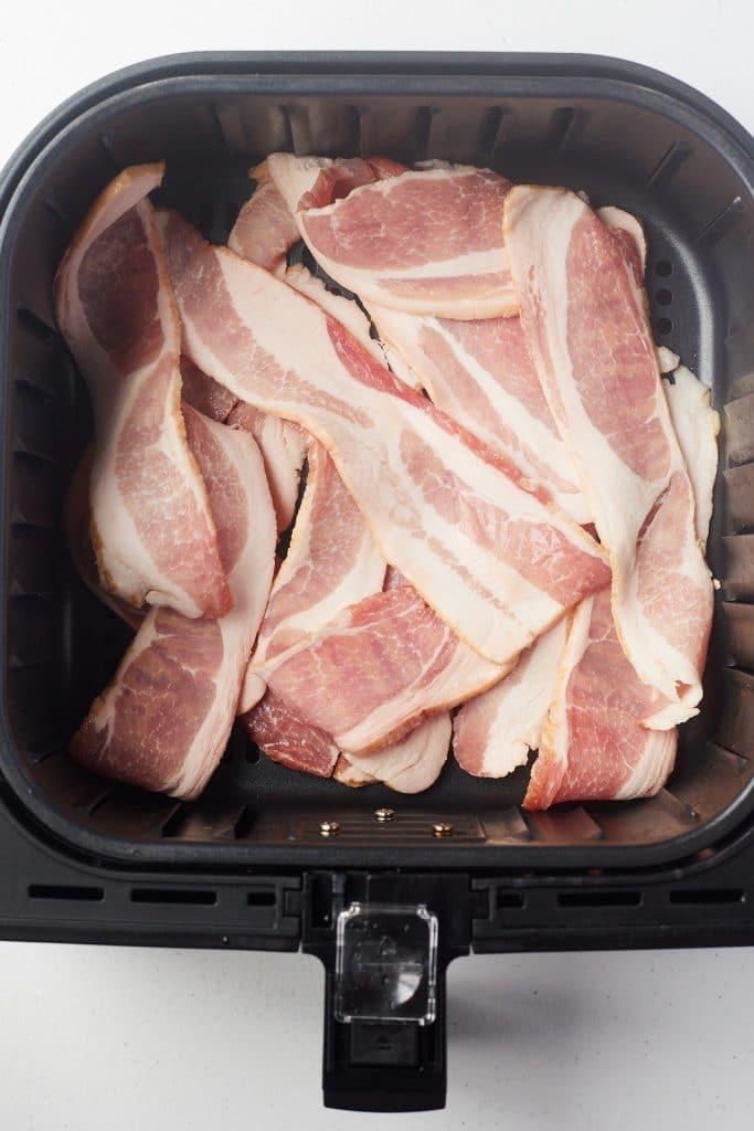 Raw bacon strips in an air fryer basket.