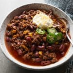 Chili served in a white bowl with a spoon.