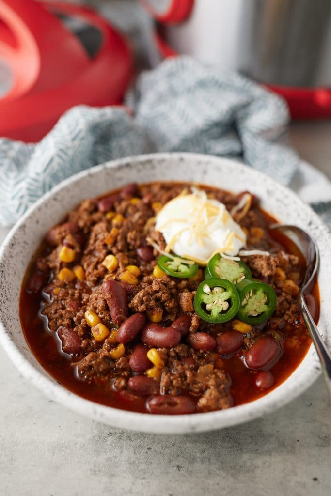 A bowl of pressure cooker chili with a spoon in it and served with toppings.