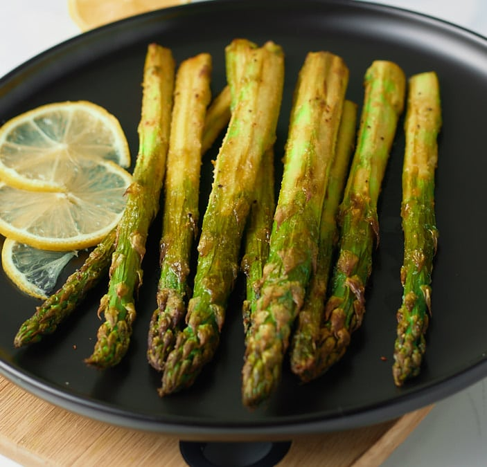 Asparagus served on a plate with slices of lemon.