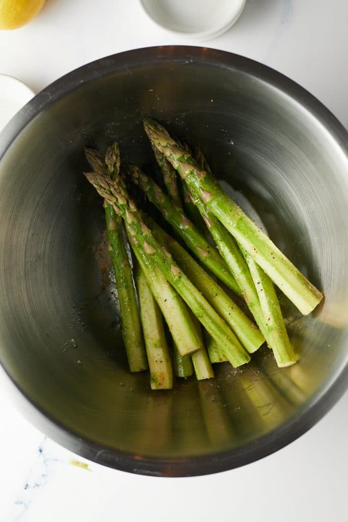 Asparagus stems being seasoned in a bowl.