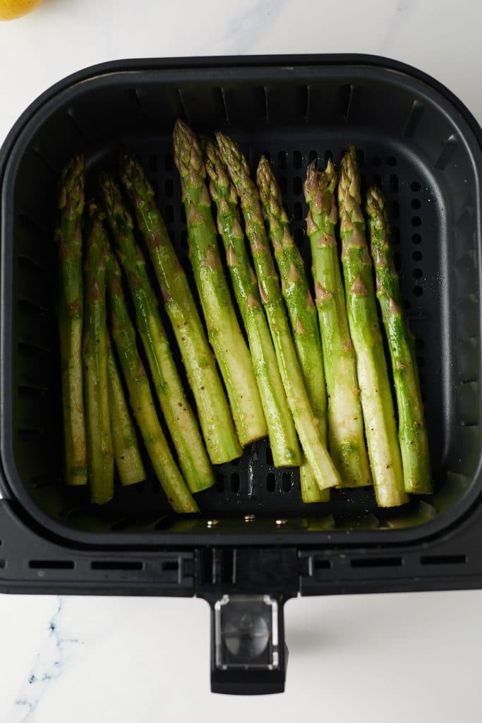 Asparagus in the air fryer basket ready to be cooked.