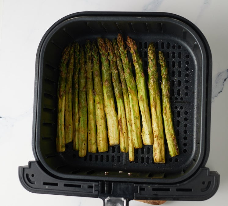 The cooked asparagus in the air fryer basket.