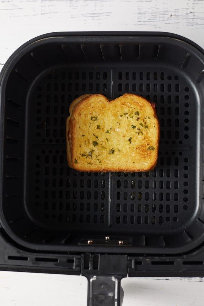 The grilled cheese in an air fryer basket.