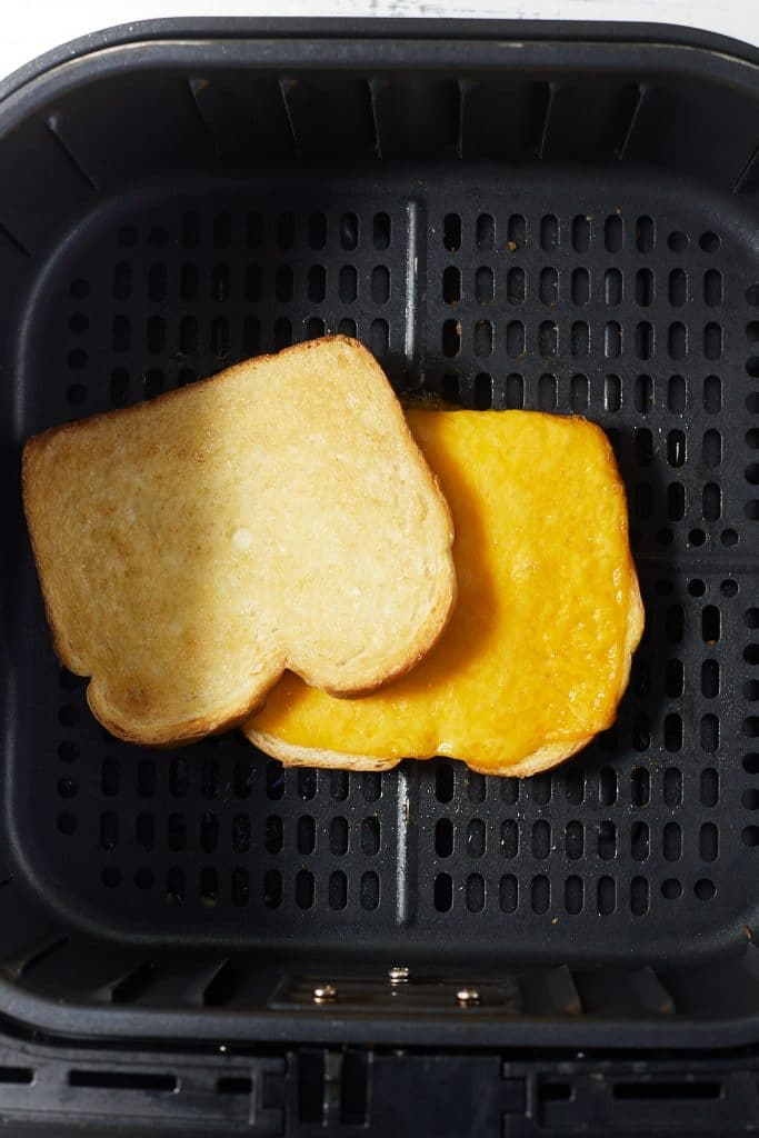 Once slice of bread on top of cheese on a piece of bread in an air fryer.