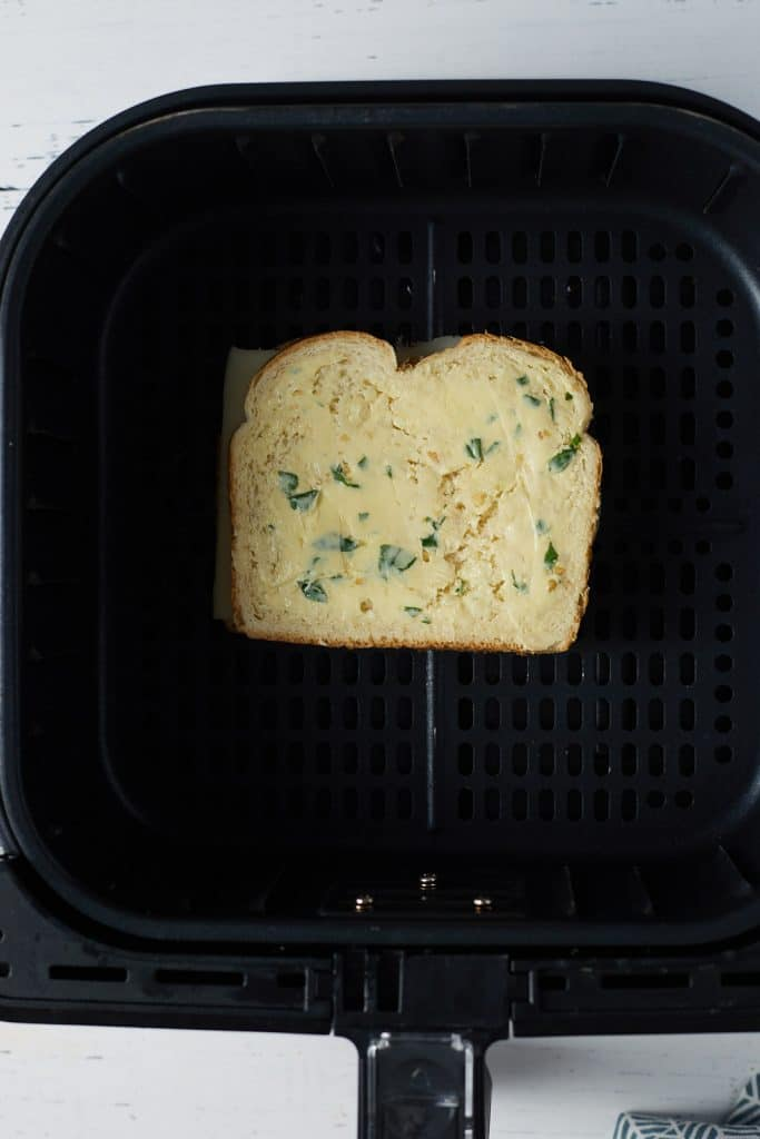 A grilled cheese in the air fryer basket before being cooked.