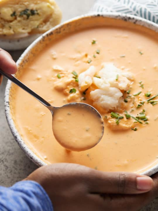 crab bisque in bowl with hands holding it