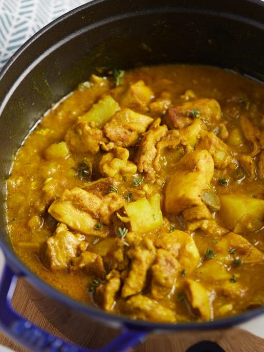 The finished chicken curry in a blue dutch oven.