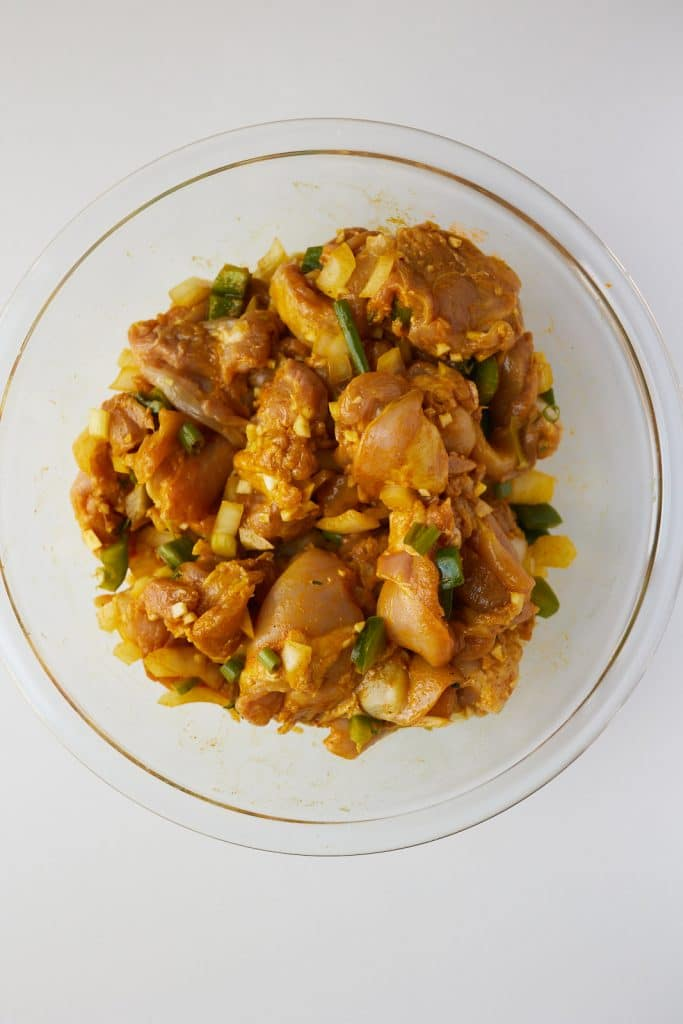 raw chicken seasoned with curry powder and spices