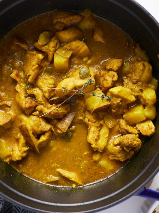 Jamaican curry chicken in blue pot with spoon on side