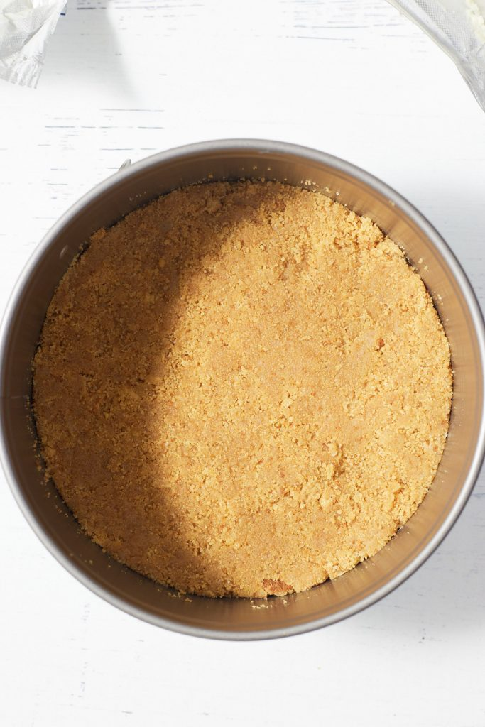 The cheesecake crust in a springform pan.