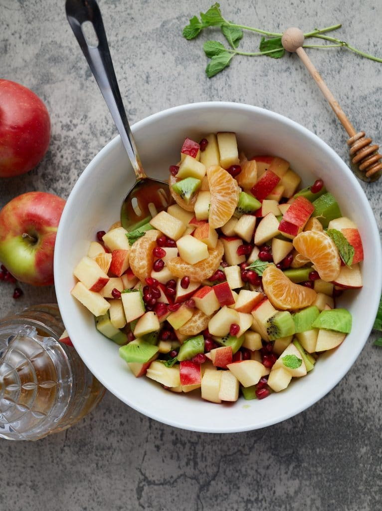 winter fruit salad in a white bowl with a honey pot and fruit surrounding it