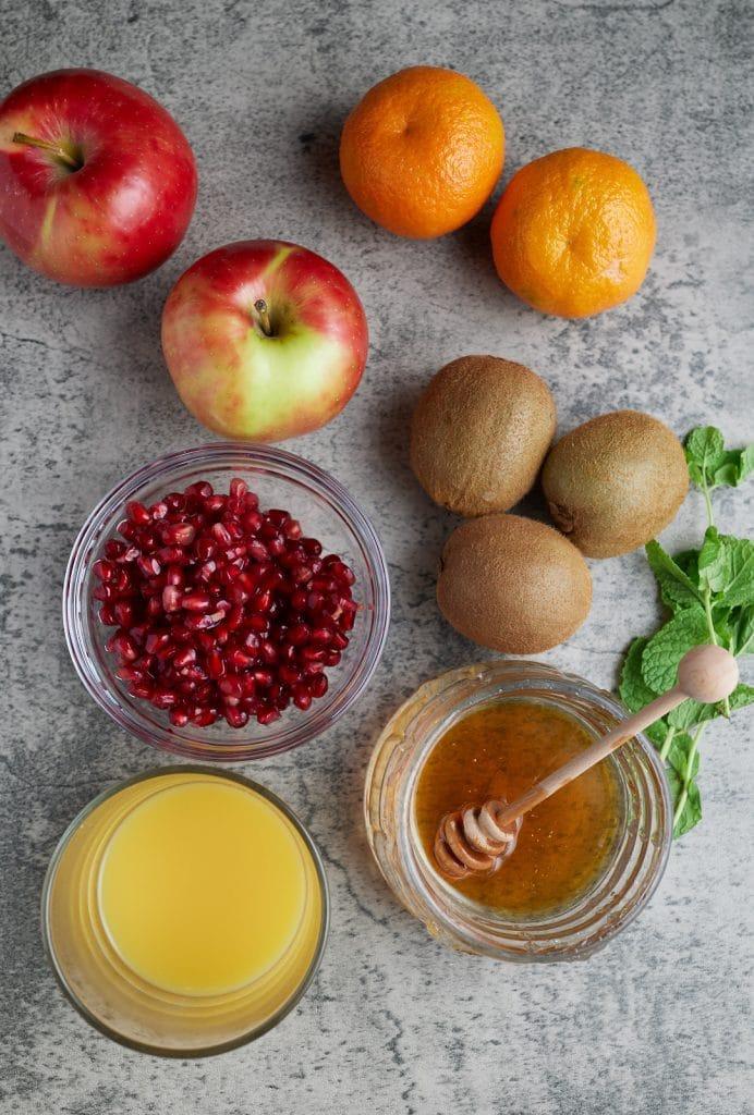 ingredient photo of apples, clementines, kiwi, promegranate seeds, honey, orange juice, and mint leaves