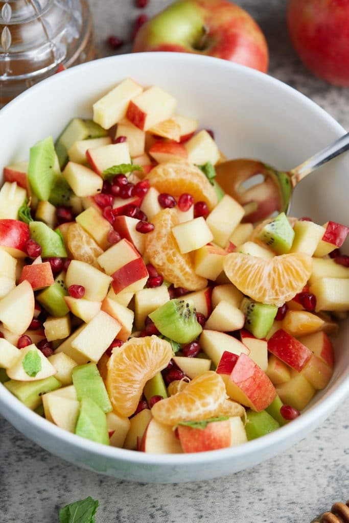 white bowl with fruit salad inside of it with spoon sticking out in corner