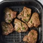 air fryer lamb chops in the air fryer basket covered with chimichurri sauce