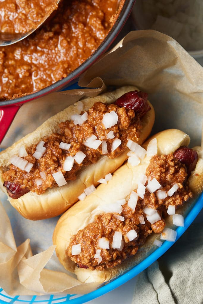 Hot dogs topped with chili on a blue plate.