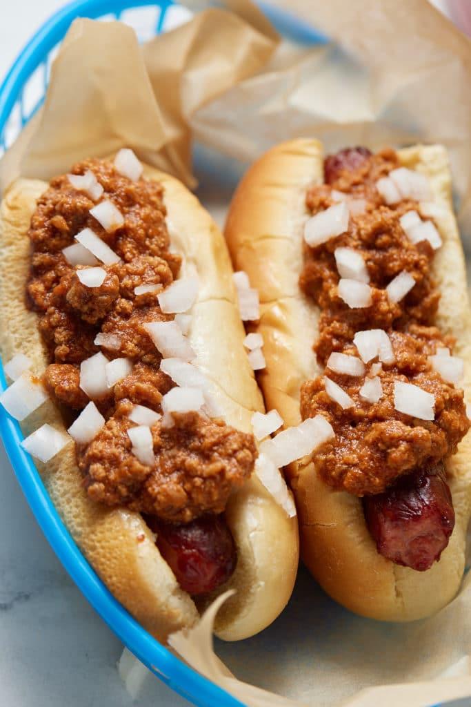 To chili hot dogs topped with sliced onions.