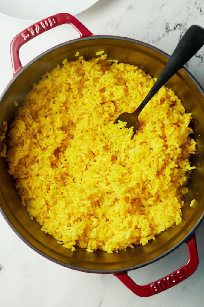 A fork in the pot of rice fluffing the grains.