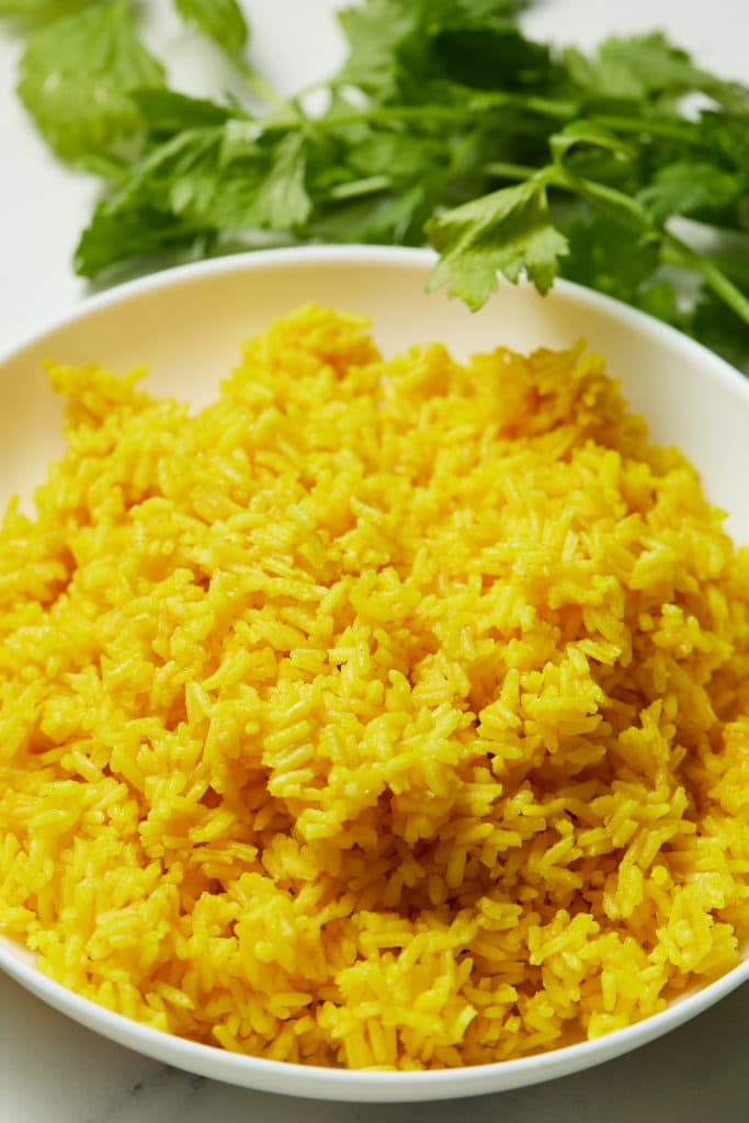 Yellow rice served on a white plate next to fresh herbs.