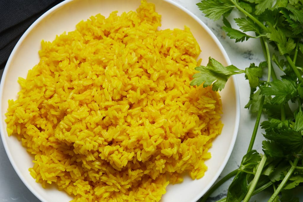 Yellow rice on a white plate next to fresh cilantro.