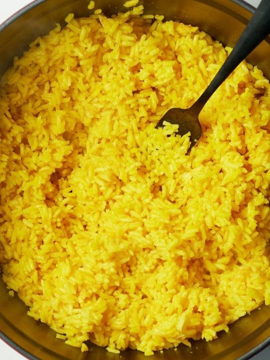 yellow rice in pot with fork sticking out