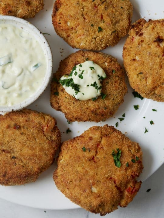 air fryer salmon patties on white plate with tartar sauce on one