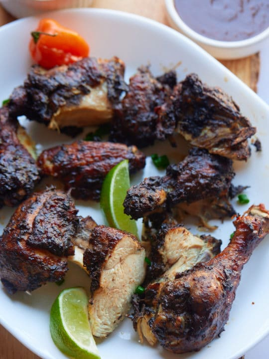 Jerk chicken served on a plate with lime wedges.