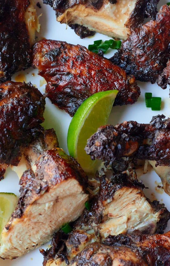 Close up of a lime wedge with pieces of marinated chicken.