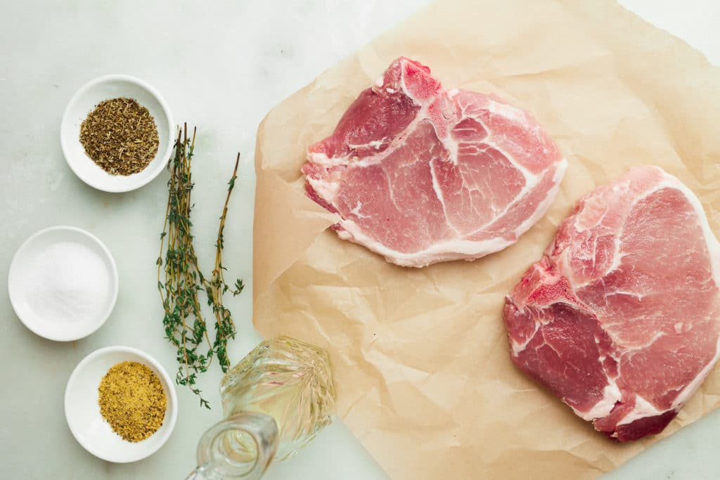 ingredients for pork chops on white table