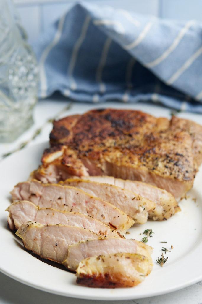 pork chops sliced in front of blue napkin
