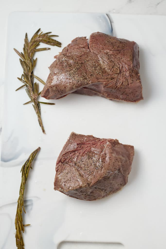 The cook steaks on a work top.