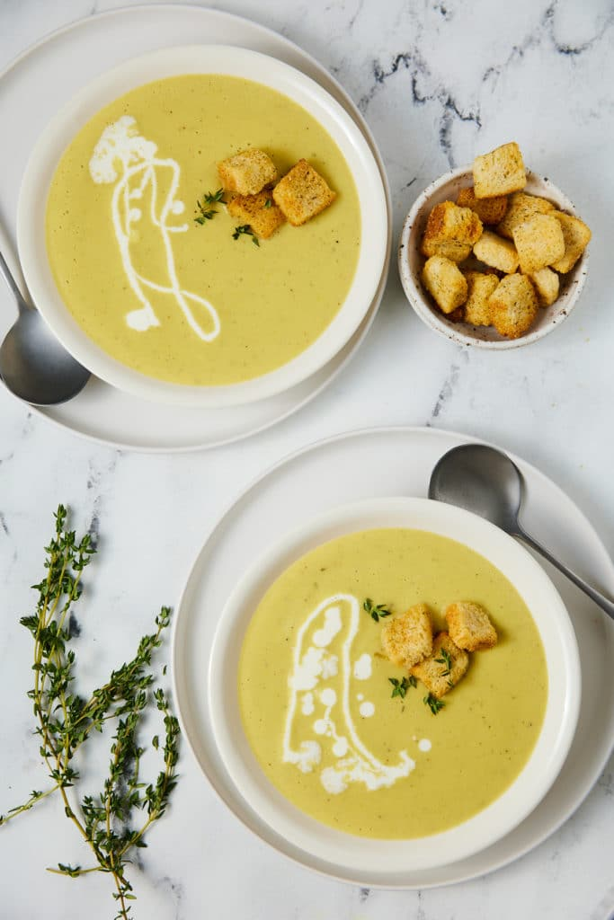 Yellow squash soup served in two white bowls.
