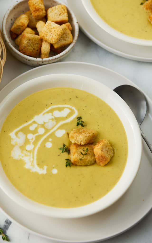 Close up of three croutons on top of the soup and a drizzle of cream.