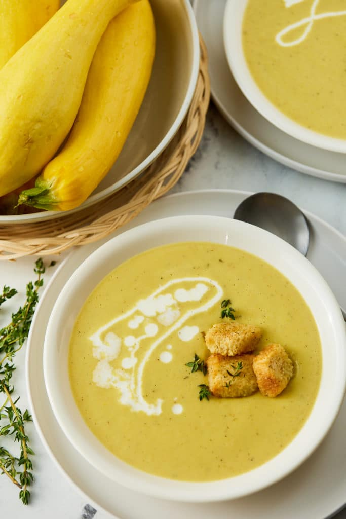 Yellow squash soup served in a white bowl with croutons.