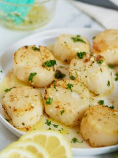 Cook scallops on a white plate next to slices of lemon.