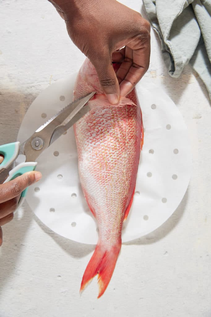 Cutting the fins off of the fish.
