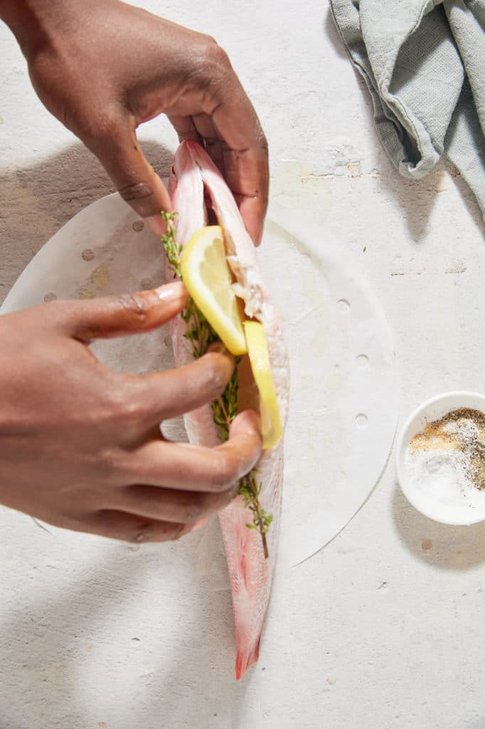 Stiffing the fish with lemon slices.