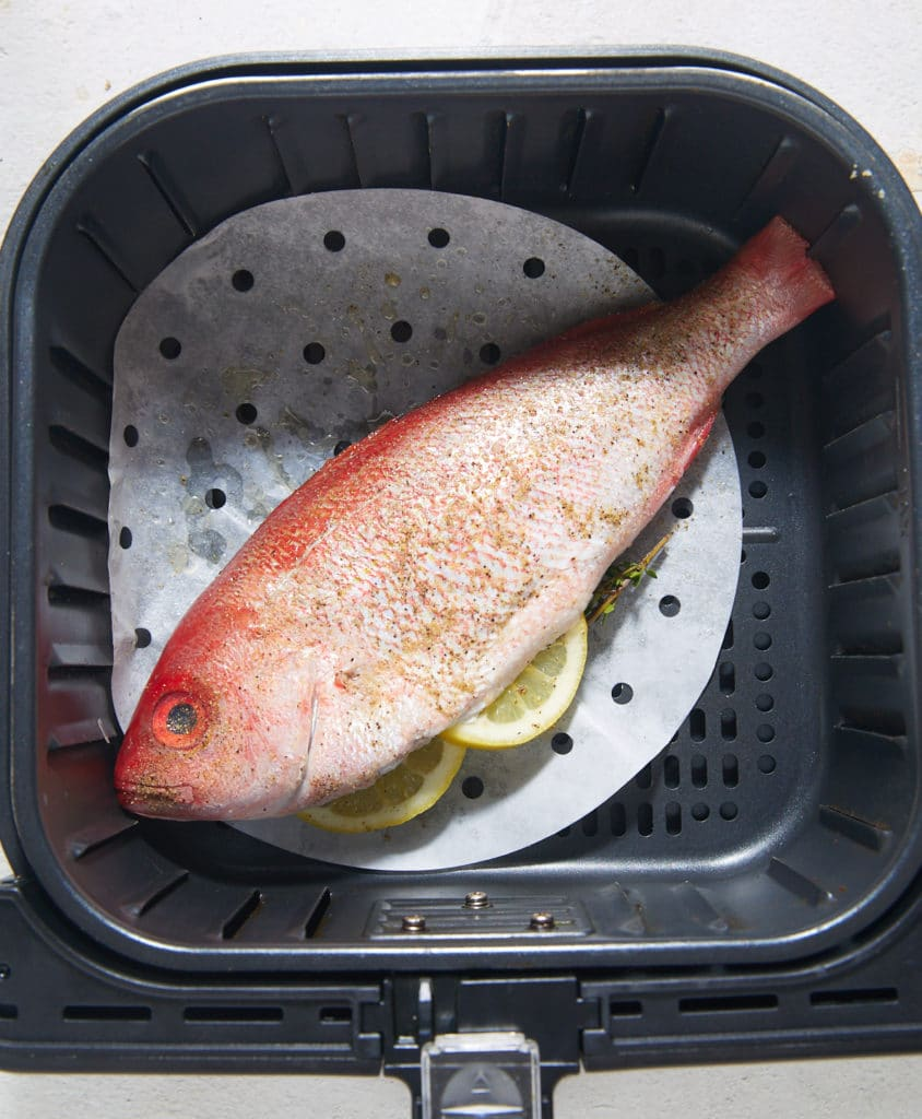 The whole fish in the air fryer basket before being cooked.