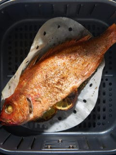 The cooked whole fish in the air fryer basket.